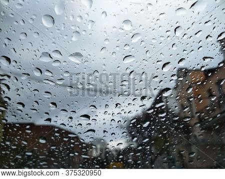 City Street Seen Through Rain Drops On The Car Windshield. Bad Autumn Weather In Rainy Day. Windshie