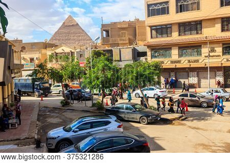 Cairo, Egypt - December 8, 2018: Busy Street In The Cairo With The Top Of The Khafre Pyramid Behind