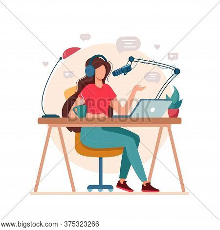 A Woman Sits At A Table With A Laptop And A Microphone, In Headphones And Records A Podcast. Concept