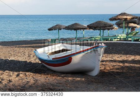 White Boat On A Deserted Beach On The Background Of Beach Umbrellas, Deck Chairs And The Sea