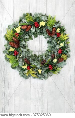 Winter & Christmas natural wreath with snow covered fir, cedar, holly, ivy, mistletoe & pine cones on rustic white wood front door background. Composition for the xmas holiday season & New Year.