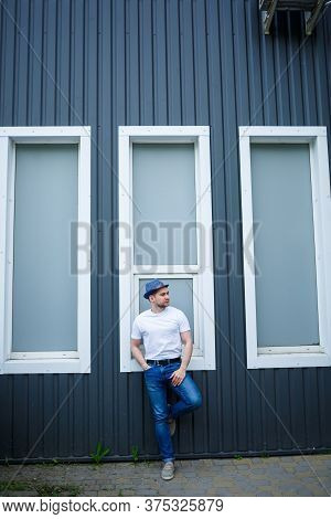 A Cool Young Man In A Stylish White T-shirt And Hat Stands Near A Gray Wall With Large Windows In Th