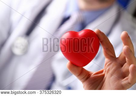 Close-up Of Persons Hand Holding Bright Red Heart. Professional Hospital Worker Wearing Medical Gown