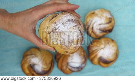 Top View Of Womens Hand Holding A Sweet Bun Over The Blurred Background With Other Buns. Bakery Conc