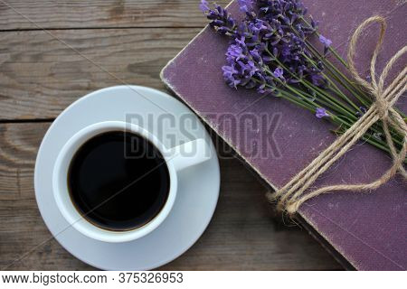 Cup Of Coffee And Old Book Decorated With Lavender Flowers And Tied With Jute Twine On Wooden Table.