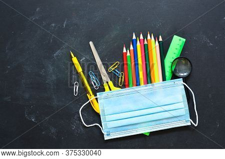 School Stationery Supplies, Medical Masks On The Blackboard. Back To School After Covid-19 Coronavir