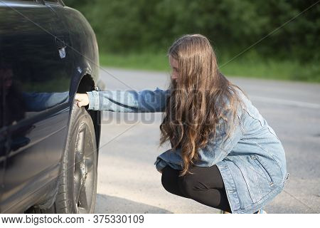 A Girl Stands Near A Car That Broke Down On The Road.