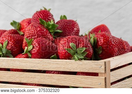 Background From Freshly Harvested Strawberries In Wooden Box. Wooden Clean Box With Bright, Red Juic