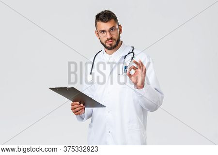 Healthcare Workers, Medical Insurance, Clinic Lab And Covid-19 Concept. Handsome Serious Doctor In W