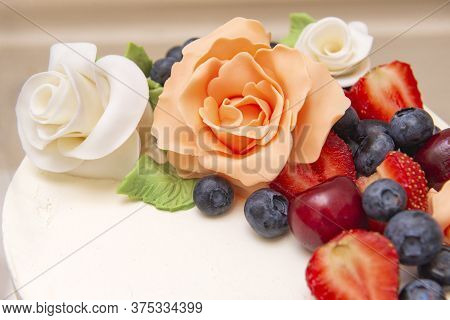 Cake With White Mastic Decorated With Beige Roses From Mastic And Fresh Berries, Blueberries, Strawb