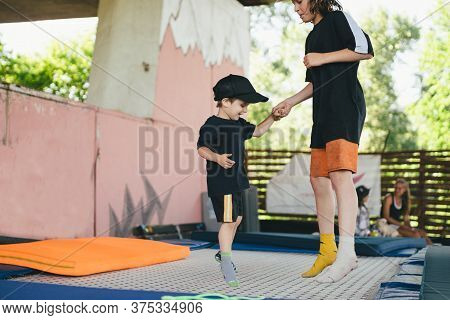 Big Brother Teaches Younger To Jump On A Trampoline. Children Active Leisure Trampolining Holding Ha
