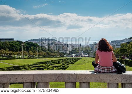 Unrecognized Tourist Woman In The Eduardo Vii Park, Looking At Lisbons Cityscape In Portugal Europe
