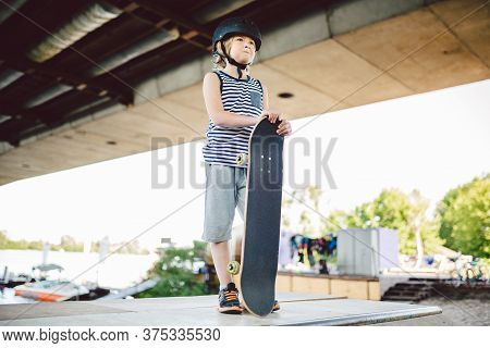 Young Boy Stands At Edge Of Half Pipe Ramp At Skateboard Park. Trendy Skateboarder Enjoying Free Tim