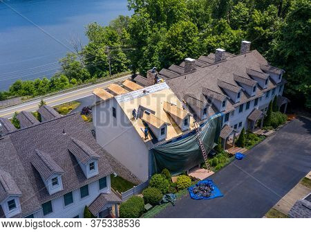 Morgantown, Wv - 7 July 2020: Aerial View Of Roofing Contractors Replacing The Old Shingles On A Tow