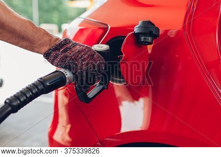 Man Pumping Gas Fuel Into Car Tank At Filling Station. Petrol Station Worker Holds Nozzle Refueling