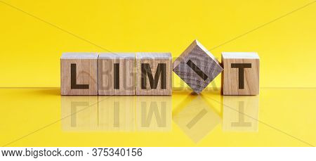 Limit Word Written On Wood Block. Limit Text On Table, Yellow Background, Concept.
