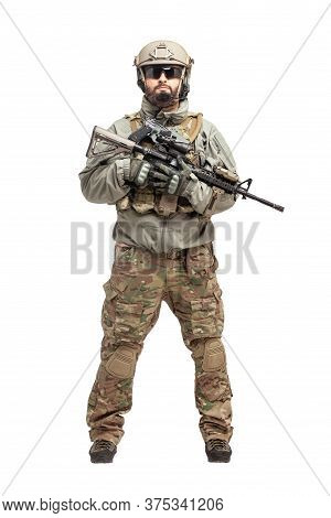 Soldier In Military Equipment With A Shotgun On A White Background, Commando In Uniform With A Weapo