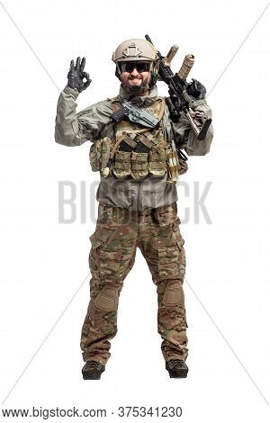 American Soldier In Military Equipment With A Rifle On A White Background Makes A Good Sign, Command