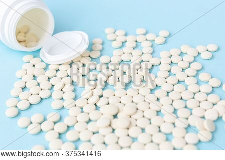 Many Pills Spilled Out Of A White Plastic Can Against A Sky-blue Background.a New Generation Antivir