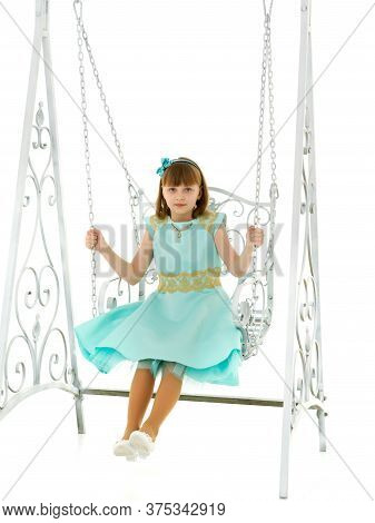 School-age Teenage Girl Swinging On A Swing. The Concept Of Rest After Class. Isolated On White Back