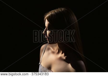 Portrait Of A Young Mysterious Girl 25 Years Old On A Dark Background In Contour Lighting.modesty An