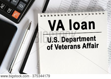 On The Table Lies A Smartphone, A Calculator And A Notebook With The Inscription- Va Loan. U.s. Depa