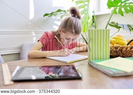 Girl Child Studying At Home, Sitting At Table. Schoolgirl Writes In Notebook, Looks Into Book, Dista