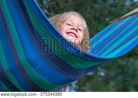 Little Happy Caucasian Girl With Blond Curly Hair Sways On Multi-colored Striped Hammock. Lifestyle.