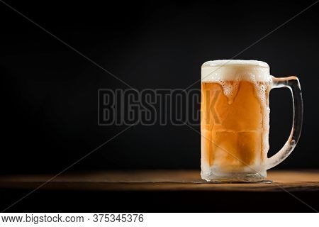 Cold Mug With Beer, With Overflowing Foam, On Wooden Table And Dark Background