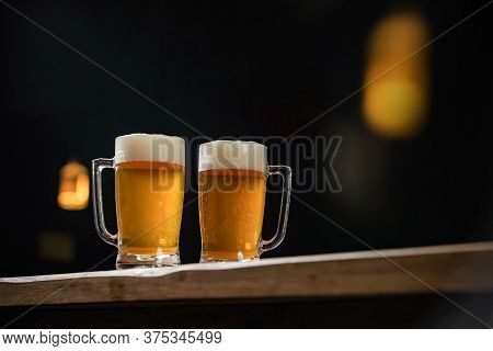 Two Cold Mugs With Beer, With Overflowing Foam, On Wooden Table And Dark Background, Space For Writi