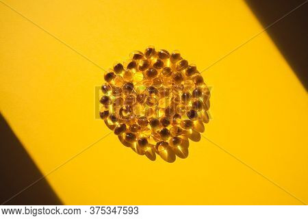 Gelatin Capsules In A Circle On A Yellow Background In The Sun. Dietary Supplement, Health Care.