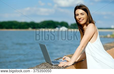 Beautiful, Smiling Woman In A White Dress With A Tablet, Pen, Laptop Phone On The Dock