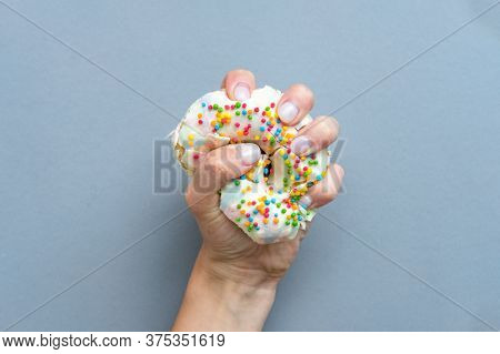 Hand Squeezes The Doughnut. One Donut With White Icing. An Overhead View Of A Doughnut With Colored