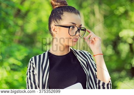 Headshot Serious Skeptical Woman Wife Looking To Side Skeptically, Doubtful With A Laptop In A City