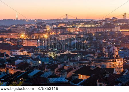 Sunset With Orange Tones From The Graça Viewpoint In Lisbon, Capital Of Portugal