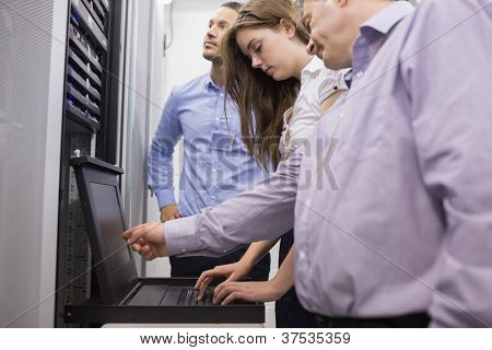 Technicians checking servers with laptop in data center