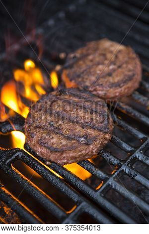 Plant Based Grilled Burger Patty With Grill Marks On A Flaming Grill