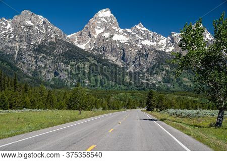 The Scenic Road Through Grand Teton National Park. Leading Lines To The Rocky Mountains In Wyoming.