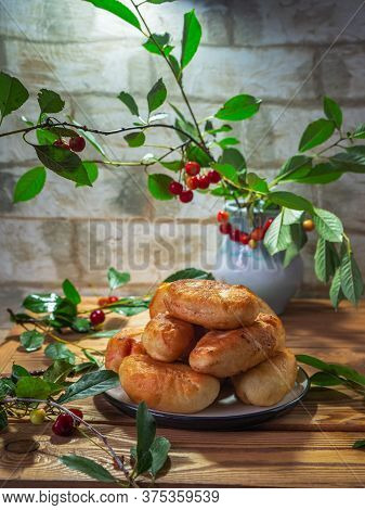 Fried Pies With Cherry Filling, Sprigs With Cherry Berries In A Blue Ceramic Vase