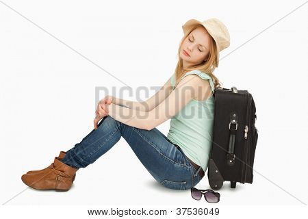 Tired woman sitting against a suitcase against white background