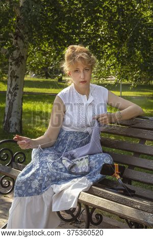Woman Sits On A Park Bench Knitting Wool Clothes On A Knitting Needle And Shows A Knitted Item Throu
