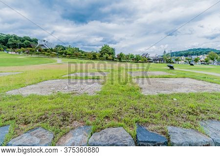 Buyeo, South Korea; July 1, 2020: Closeup Of Large Square Slabs Of Stone In Ground At Archeological