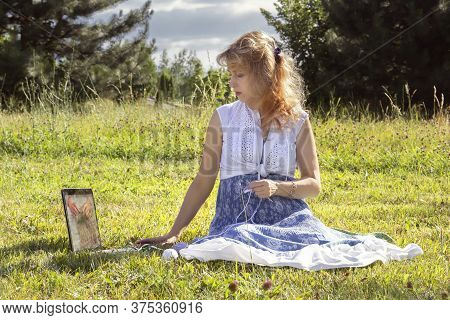 Woman Sits On The Grass In A Park Knitting Wool Clothes On Knitting Needles And Watching Lessons Or