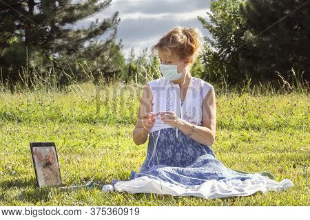 Woman With A Medical Mask On Her Face Sits On The Grass In A Park Knitting Wool Clothes On Knitting
