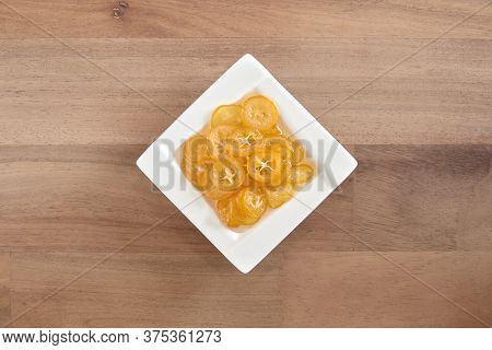 Candied And Sliced Kumquats On A Small Square White Plate, On A Wooden Base. Top View.