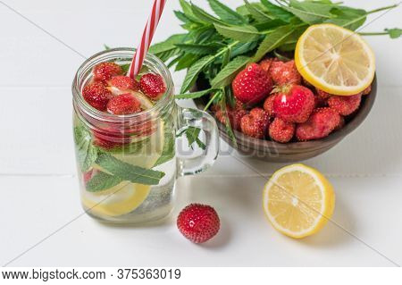 A Bowl Of Berries And Lemon And A Mug Of Cold Refreshing Drink On A White Table. Freshly Prepared Re