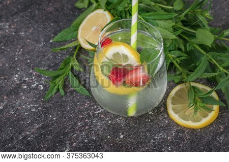 Refreshing Water With Lemon, Mint And Berries In A Glass Glass. Freshly Prepared Refreshing Drink Wi