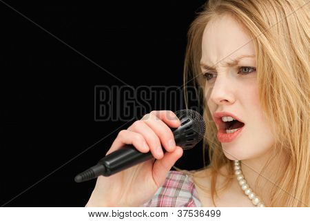 Woman singing while frowning against black background