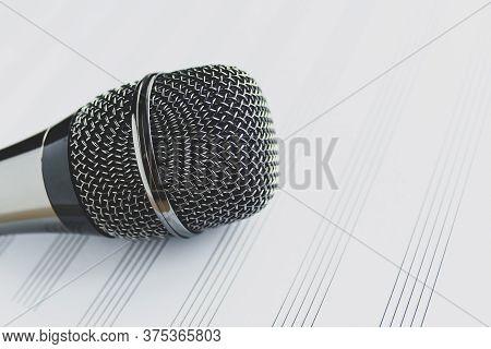 Microphone On A Blank Musical White Sheet Close Up. Singing, Writing Music, Karaoke Online, Creativi