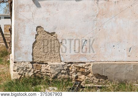 Plaster Peeling Off Brick Wall. The Foundation Of A Residential Building Is Gradually Collapsing.